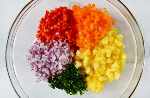 Glass bowl with diced orange and red bell peppers, diced pineapple, minced cilantro and diced red onion.