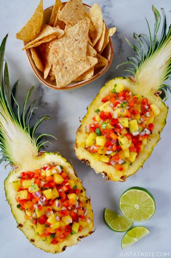 Two pineapple boats filled with The Best Pineapple Salsa with a cut lime and small bowl of tortilla chips.