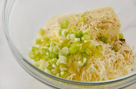 A glass bowl containing butter, mayo, cheese and scallions