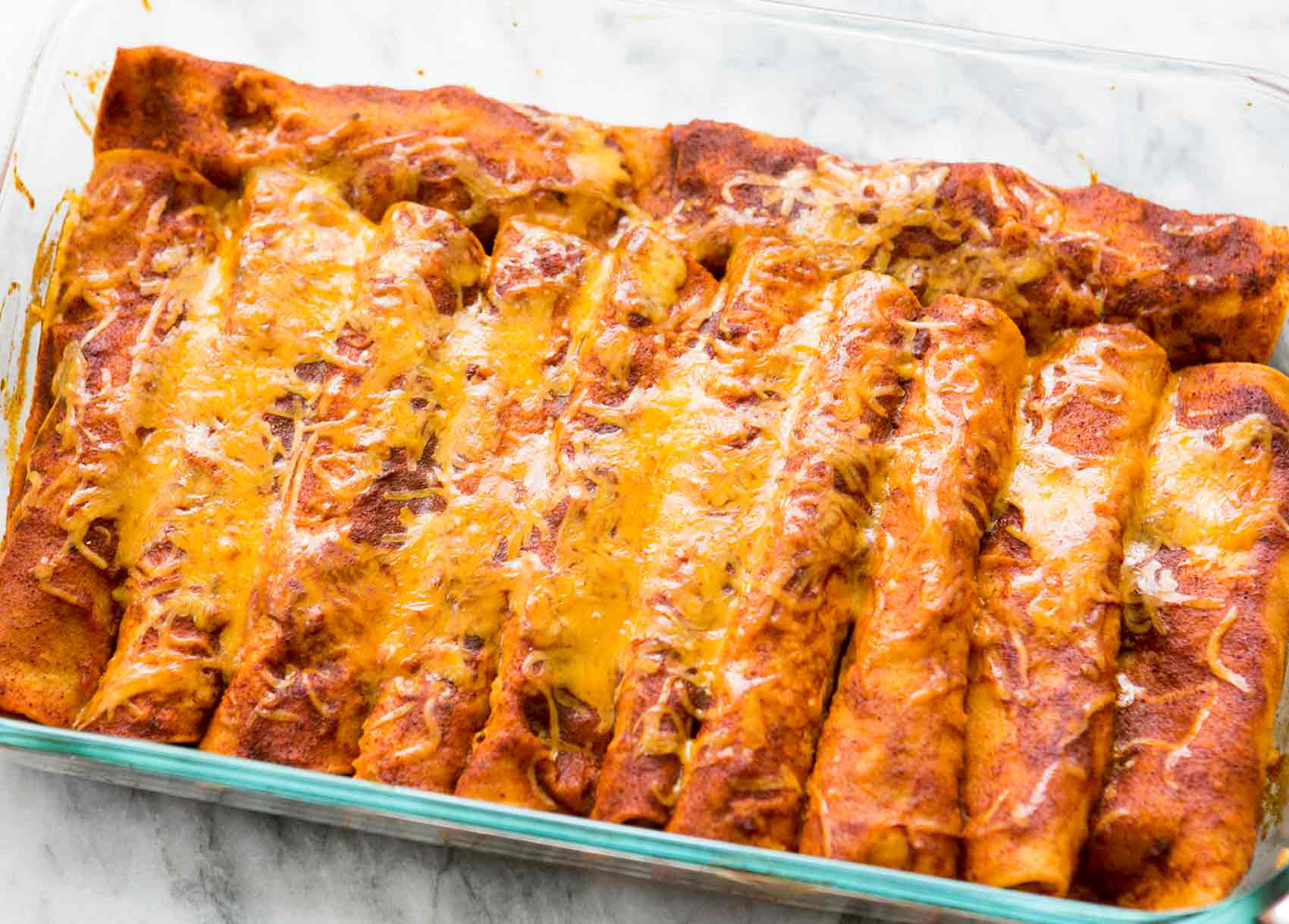 Easy Chicken Enchiladas in pan covered in red chili sauce and cheese