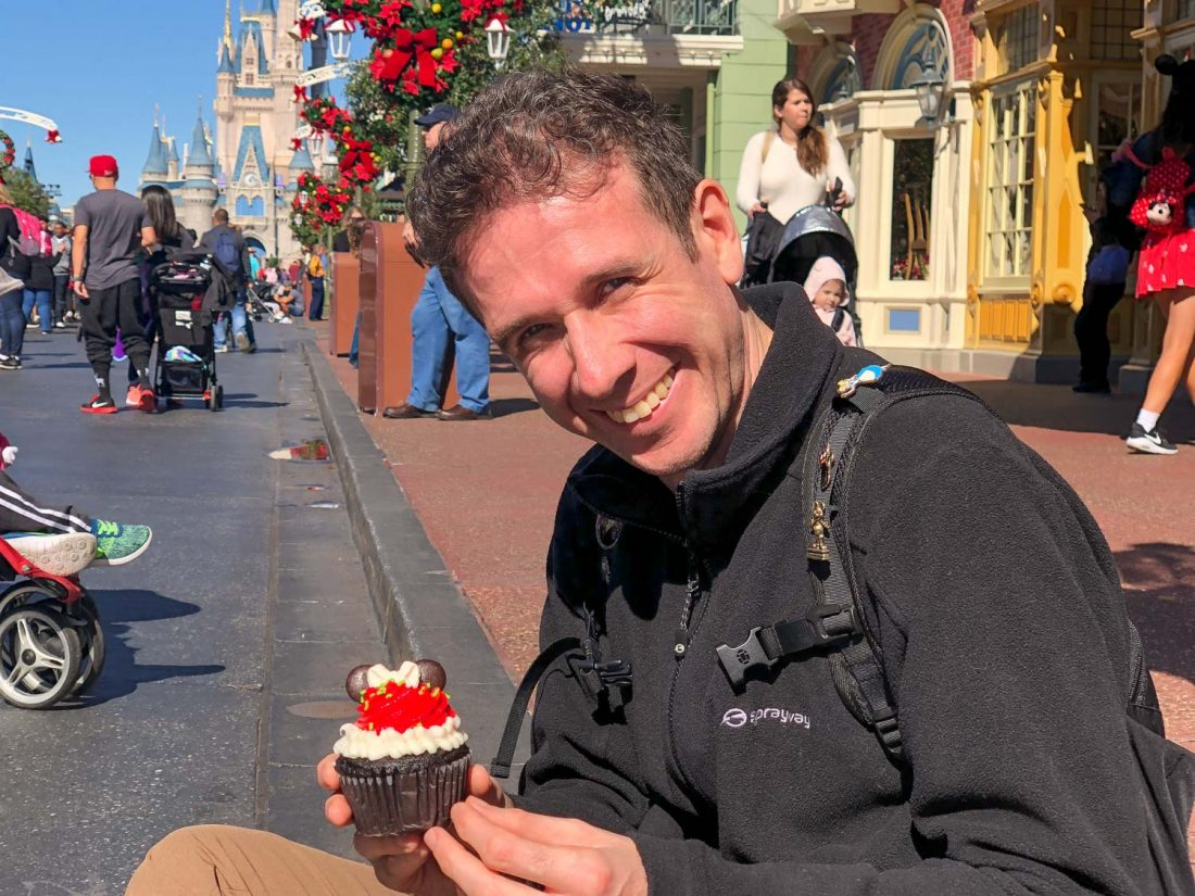 Simon eating a Mickey cupcake at Disney World Magic Kingdom Main Street