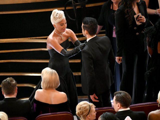 Lady Gaga adjusts butterfly Ramie Malek