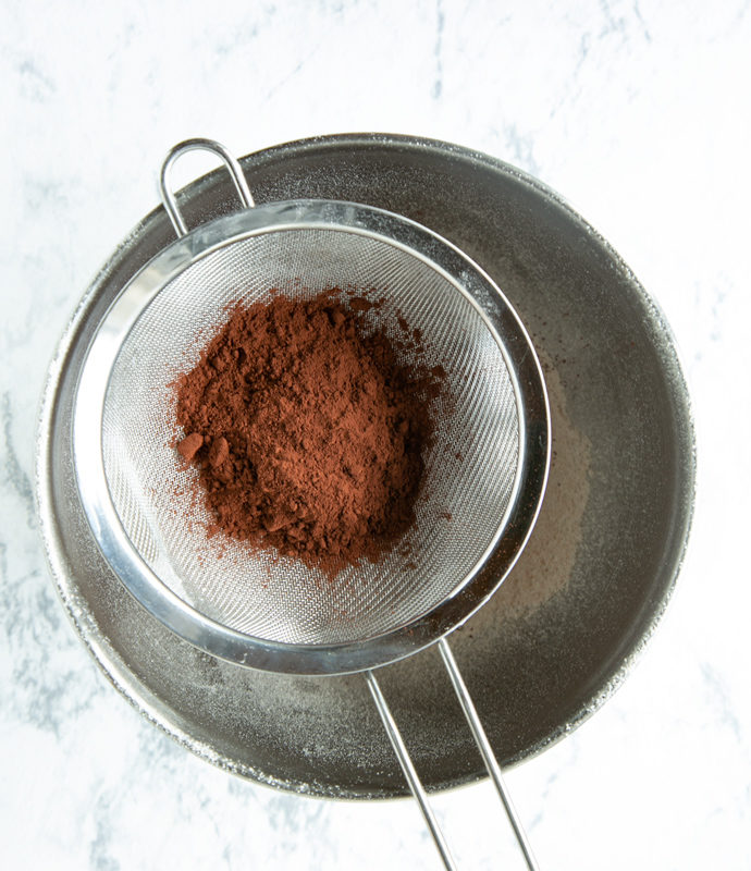 vegan chocolate muffins method step 2: cocoa powder in sifter over metal bowl