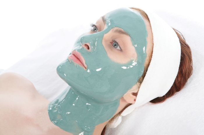 Woman lies with alginate mask on her face.