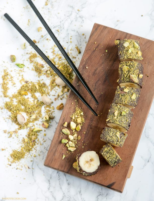 chocolate banana sushi with pistachios on top on a wood board, with chopsticks on the side, and crumbled pistachio in the background