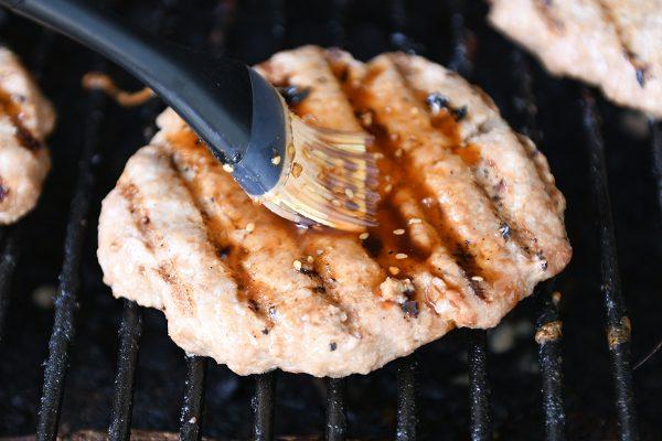 Brushing grilled turkey burger with teriyaki sauce.