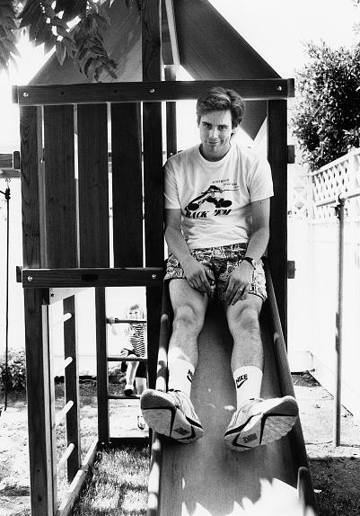 Jim Carrey on a children's slide