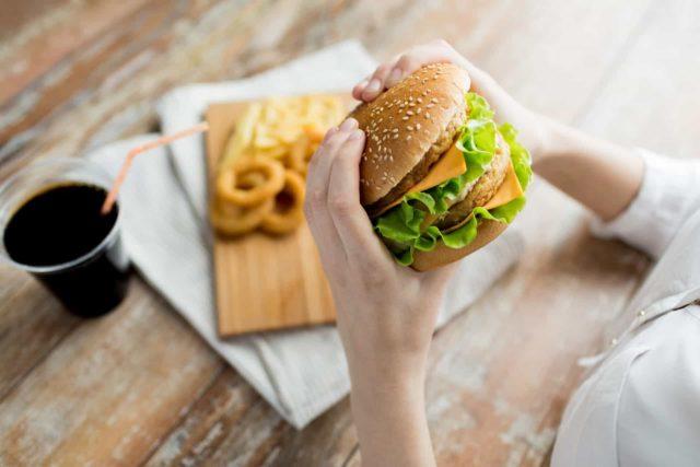 girl holds hamburger