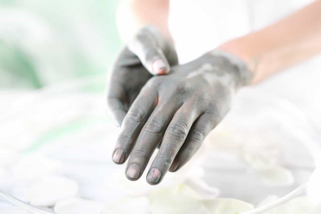 mud mask on the hands of a girl