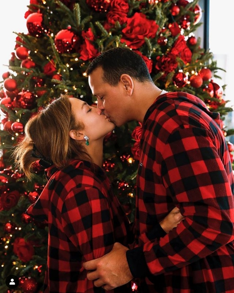 Jennifer Lopez and Alex Rodriguez on the background of the Christmas tree