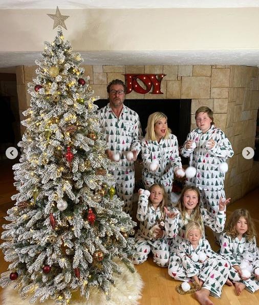 tori spelling with family near christmas tree
