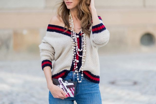 girl in a cardigan on one shoulder and jeans