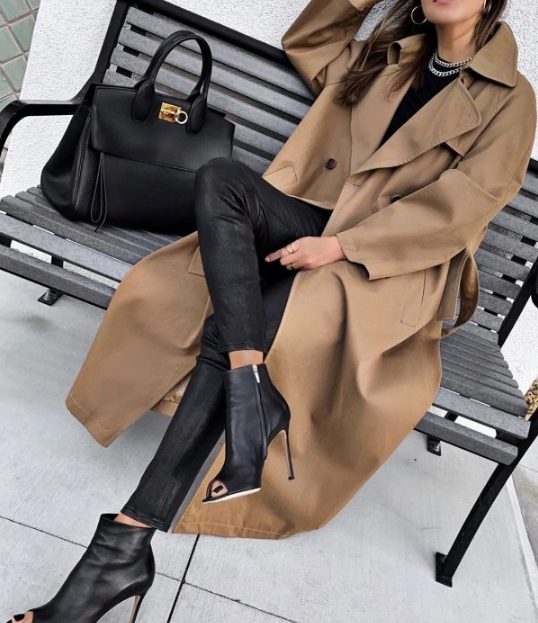girl sitting on a bench in a beige trench coat